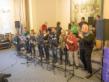 Eine Gruppe Menschen steht zusammen. Einige stehen an Mikrofonen uns singen. Die anderen spielen Instrumente.