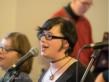 Ein Mädchen mit schwarzen Haaren und Brille steht vor einem Mikrofon und singt.
